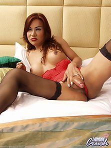 Red Dress Wear Sexy Ladyboy Displaying Her Cock on Her Bed in Naughty Action