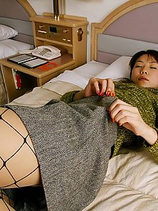 Cute Japanese teen in fishnet stockings plays with her feet and shows