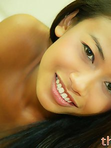 Teen Thai girl poses on the bed