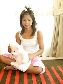 Asian teen plays with a teddy bear in bed